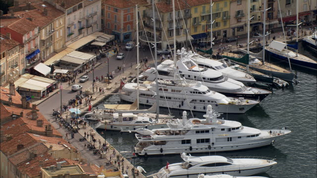 AERIAL Traffic and pedestrians pass through busy harbor/ Saint-Tropez, France