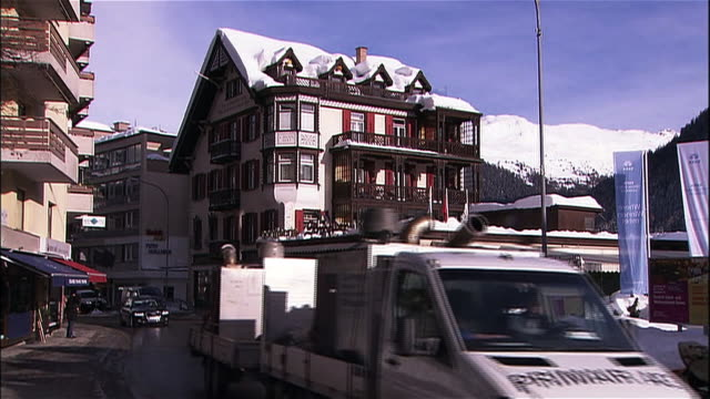 Traffic and pedestrians pass through the snowy mountain town of Davos, Switzerland.