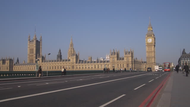 ws traffic and pedestrians passing over westminster bridge with houses of parliament in background/ london, england - ビッグベン点の映像素材/bロール