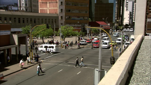 stockvideo's en b-roll-footage met traffic and pedestrians speed across a busy intersection. - johannesburg