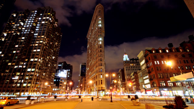 traffic and pedestrians travel past the flatiron building at night. - flatiron building manhattan stock videos & royalty-free footage
