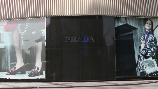 Traffic and pedestrians walk past a Prada SpA store in Beijing China on Tuesday Sept 9 Pedestrians walk past a fan spraying mist in front of a...