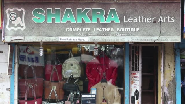 vídeos y material grabado en eventos de stock de traffic and pedestrians with umbrellas walk past leather goods stores in the dharavi area of mumbai, india, on tuesday, july 18 pedestrians with... - iva
