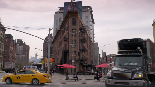 traffic and people moving along the divide between hudson street and 9th avenue in the meatpacking district - inquadratura fissa video stock e b–roll