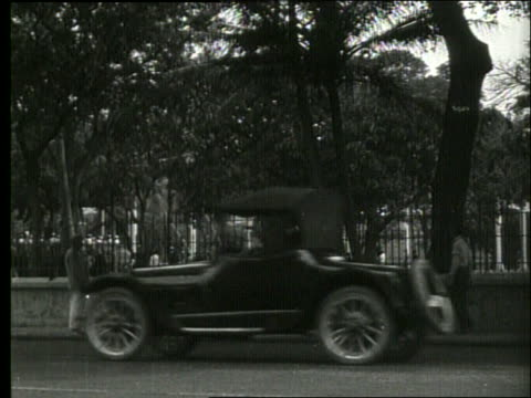 B/W traffic and people on street with park in background / Honolulu / 1919 / NO SOUND