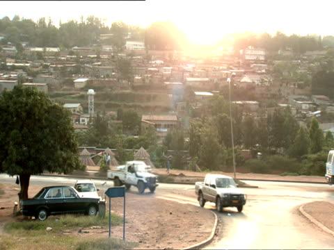 ws pan traffic around kigali with cityscape on hill and pedestrians on sidewalks / kigali, rwanda  - ルワンダ点の映像素材/bロール