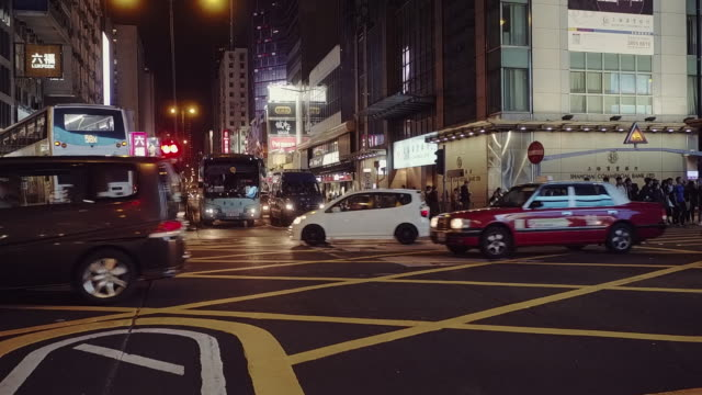 traffic at a road intersection at night seen from a low angle perspective, mong kok, kowloon, hong kong - mong kok stock videos & royalty-free footage