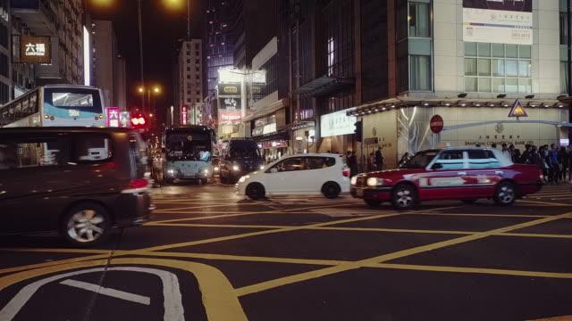 vídeos de stock e filmes b-roll de traffic at a road intersection at night seen from a low angle perspective, mong kok, kowloon, hong kong - mong kok