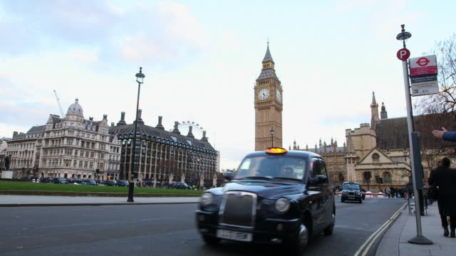 ws traffic at city of westminster with big ben in background / london, england, united kingdom - ビッグベン点の映像素材/bロール