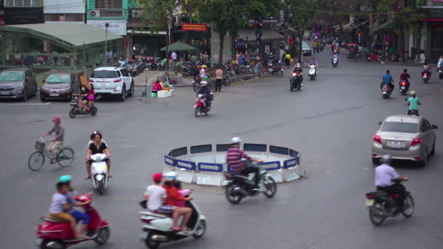 traffic at hanoi vietnam. roundabout high angle view. motorbikes and cars directly above. hang da market - roundabout stock videos & royalty-free footage