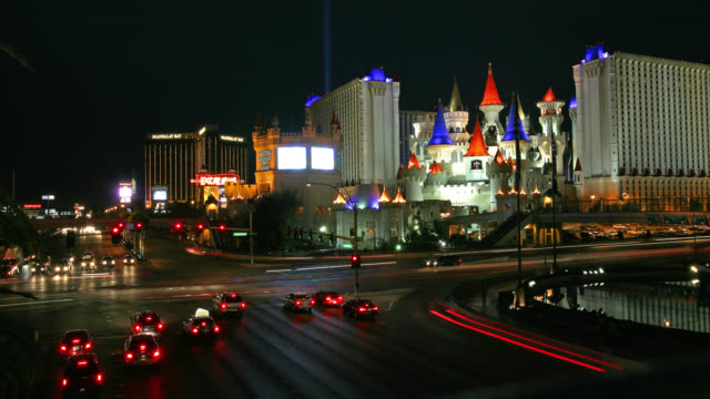 time lapse wide shot traffic at intersection in front of excalibur hotel and casino with mandalay bay in background at night - mandalay bay resort and casino stock videos and b-roll footage