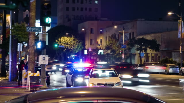WS ZI T/L Traffic at intersection of change and LAPD police car in background / Hollywood, California, USA.