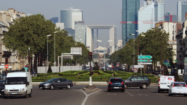vídeos de stock, filmes e b-roll de zo traffic at porte maillot with high-rise buildings of the la defense business district behind / paris, ile de france, france - formato letterbox