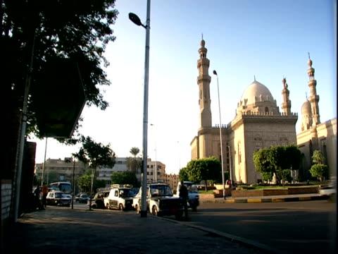 ms, pan, traffic at sultan hassan madrassa, cairo, egypt - fächerpalme stock-videos und b-roll-filmmaterial