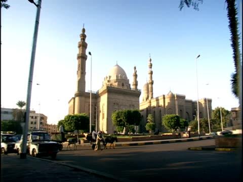 vídeos de stock e filmes b-roll de ms, pan, traffic at sultan hassan madrassa, cairo, egypt - fan palm tree