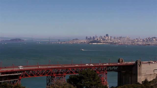 traffic at the entry to the golden gate brigde with san francisco in the background - sunny video stock e b–roll