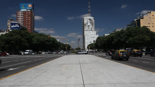 vidéos et rushes de traffic at the street july 9 avenue. its name honors argentina's independence day, july 9, 1816. a sign of evita can be seen in the background. - street name sign
