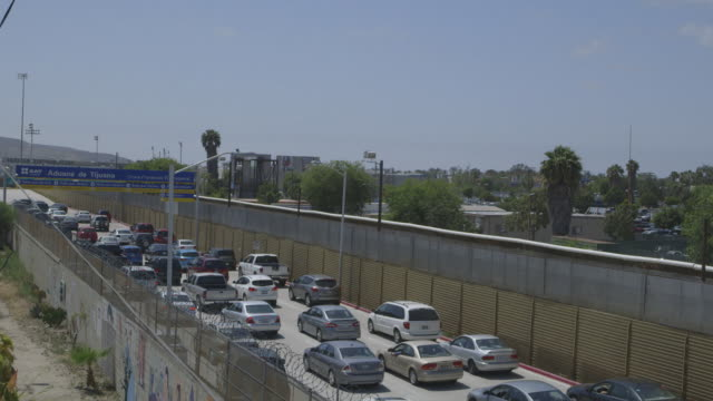 vidéos et rushes de traffic at us-mexico border, wide-shot - major road