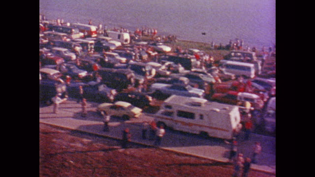 traffic blocks the highway, the ocean is punctuated by small boats and crowds of people line every road and path - 1981 stock videos & royalty-free footage