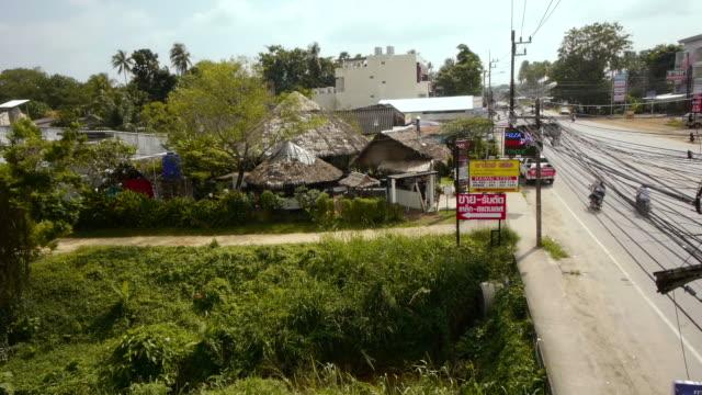 traffic by a village in phuket, thailand. - spoonfilm stock-videos und b-roll-filmmaterial