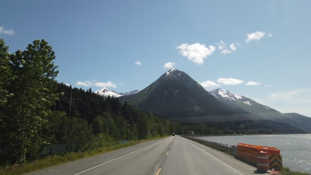 traffic cone and dashboard camera point of view of driving towards snowcapped mountains in alaska in a sunny day - traffic cone stock videos & royalty-free footage