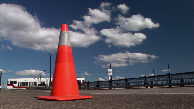 ms, traffic cone on road, car and train passing in background - traffic cone stock videos & royalty-free footage