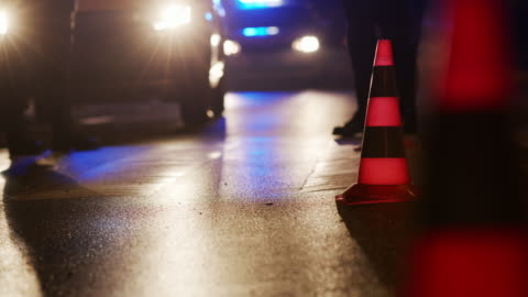 traffic cone on the road. place of an accident. transport. road traffic at night. sign - traffic accident stock videos & royalty-free footage