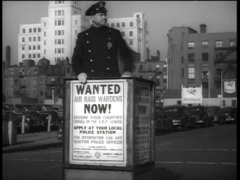 vídeos de stock, filmes e b-roll de traffic cop and sign seeking volunteers for air raid wardens / boston, massachusetts, united states - air raid