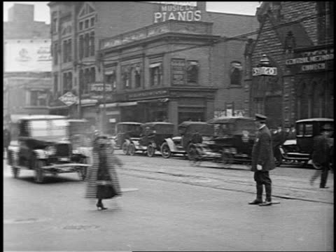 b/w 1920 traffic cop grabbing woman crossing street from path of oncoming car on city street - 1920 stock-videos und b-roll-filmmaterial