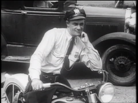 B/W 1939 traffic cop sitting on motorcycle shaking head / documentary