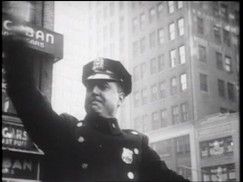 b/w 1939 traffic cop waving on traffic on city street / nyc / documentary - trillerpfeife stock-videos und b-roll-filmmaterial