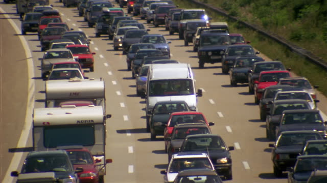Traffic crawls along a three-lane freeway.