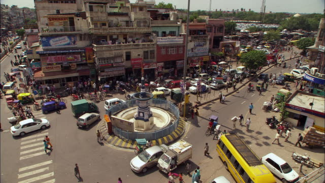 Traffic crosses junction on busy streets of New Delhi, India. Available in HD.