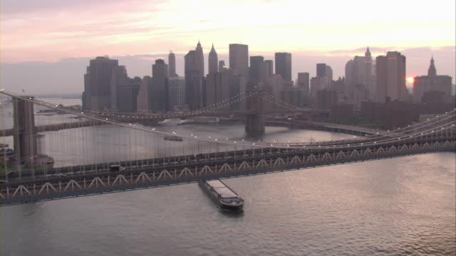 vídeos de stock, filmes e b-roll de traffic crosses the manhattan bridge at golden hour. - rio east