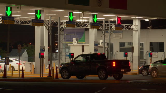 ws traffic crossing into mexico at us border at night - control stock videos & royalty-free footage