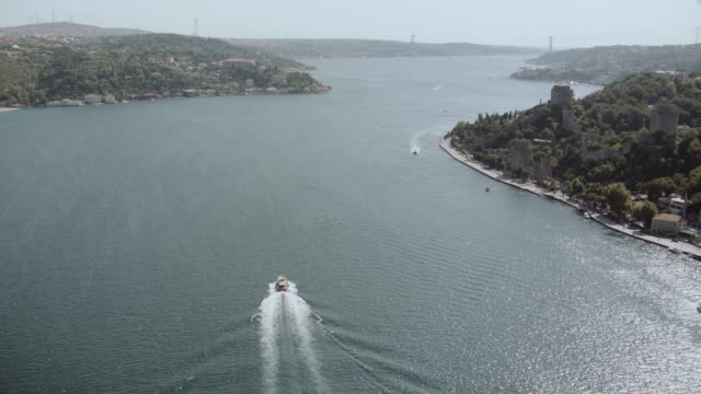 aerial traffic crossing the bosphorus bridge as a yacht drives out to sea / istanbul, turkey - july 15 martyrs' bridge stock videos & royalty-free footage