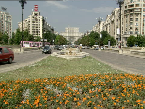 Traffic drive along green Unirii Boulevard Ceaucescu's Palace in background Bucharest