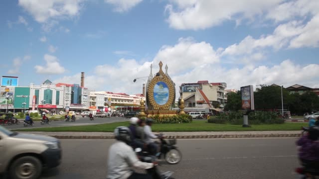 vidéos et rushes de traffic drive past a monument on a road in phnom penh cambodia on wednesday sept 14 motorcycle traffic wait for a signal from a traffic officer on a... - asiatique de l'est et du sud est