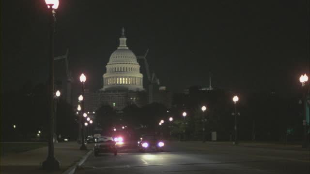 vídeos de stock, filmes e b-roll de traffic drives along a street away from the u.s. capitol in washington, d.c. - capitol building washington dc