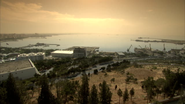 traffic drives around the base of a hill in the port city of baku. available in hd. - baku video stock e b–roll