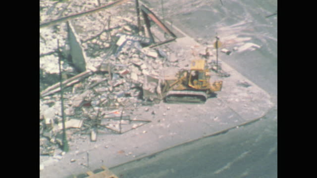 vidéos et rushes de traffic drives by a devastated city block as a bulldozer cleans up the mess - 1967