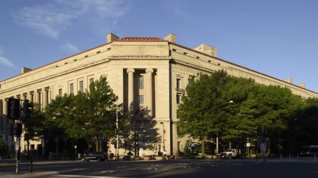 Traffic drives by the Robert F. Kennedy Department of Justice Building.