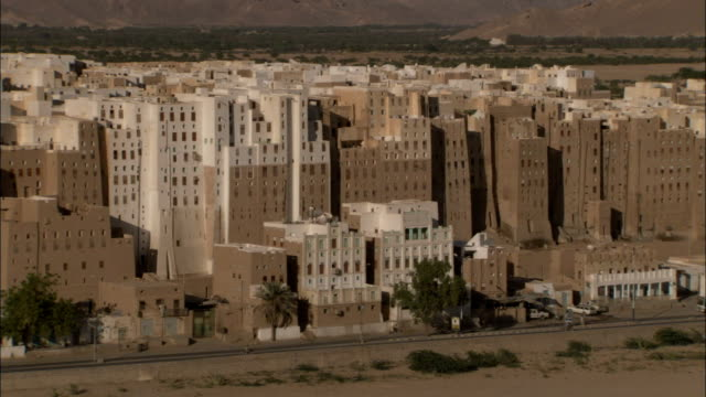 Traffic drives by towering mud-brick high rises in the town of Shibam Yemen.