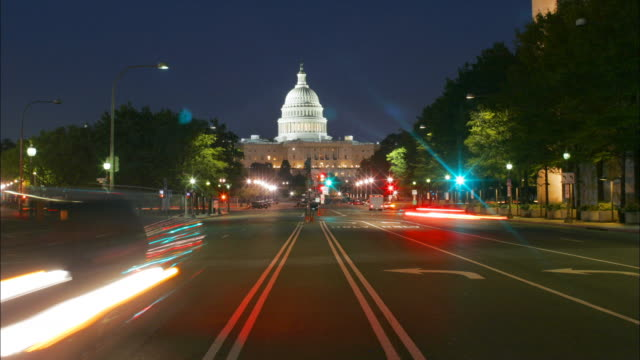 Traffic drives down Pennsylvania Avenue in front of the U.S. Capitol Building at night in Washington, D.C.