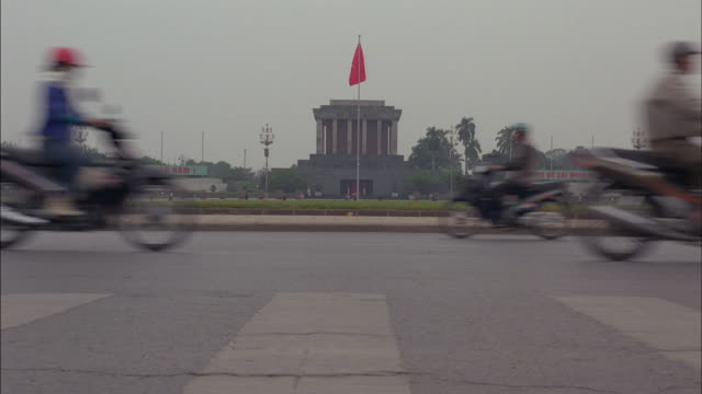 traffic drives near the ho chi minh mausoleum in hanoi, vietnam. - hanoi stock videos and b-roll footage