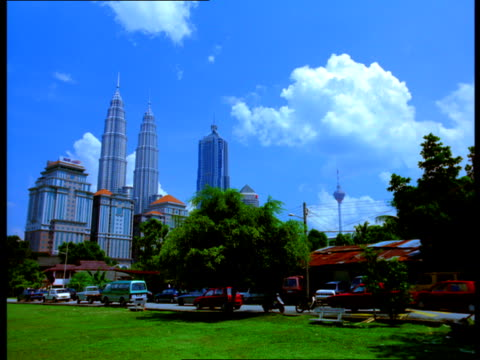 Traffic drives near the Petronas Towers, the Bangunan AM Finance building, and the Menara Telecommunications Tower in Kuala Lumpur, Malaysia.