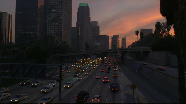 traffic drives on a freeway along the los angeles skyline at dusk. - headlight stock videos & royalty-free footage