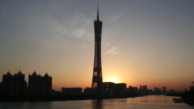 vídeos y material grabado en eventos de stock de traffic drives on liede bridge in guangzhou china canton tower stands on the pearl river in guangzhou china buildings stand in the zhujiang new town... - guangzhou