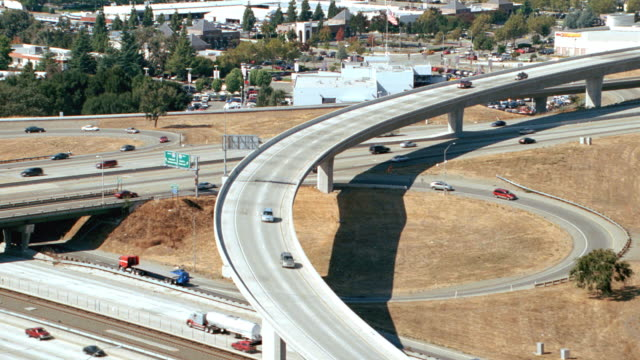 stockvideo's en b-roll-footage met traffic drives over a freeway interchange near silicon valley, california. - birthplace of silicon valley