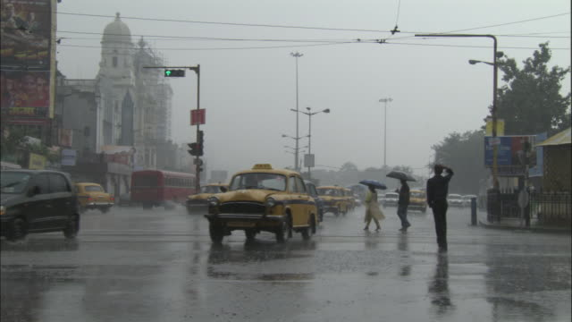 Traffic drives over crossroads in rain, Kolkata, India Available in HD.